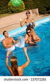 Young friends playing ball in water, laughing, having fun at summertime.