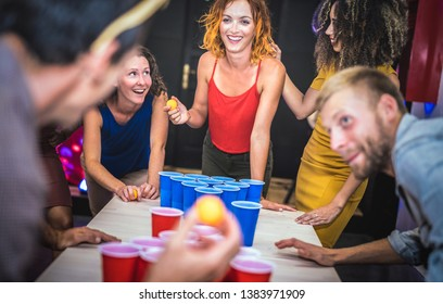 Young friends playing beer pong at youth hostel - Free time travel concept with backpackers having unplugged fun at guesthouse - Happy people on playful genuine attitude - Vivid vignetting filter