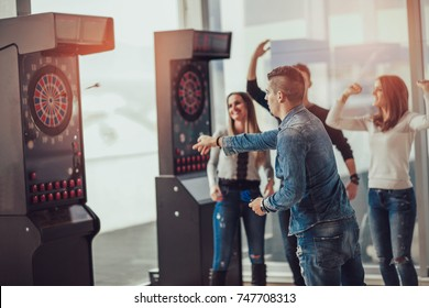 Young friends playing darts in a club