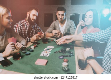 Young Friends Playing Poker on Party at Home. Playing Games. Indoor Fun. Young Girl. Young Guy. Sitting at Table. Party with Friends. Indoor Activities Concept. Gambling. Card Games.