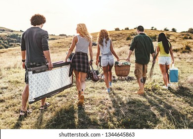 The young friends are preparing for camping. They're holding a resting chair, picnic basket, and other necessaries and searching for a suitable place in a sunset.