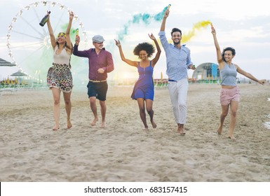 Young friends running with smoke bombs champagne bottle on the beach at sunset - Happy people having fun in summer vacation - Friendship, youth and party concept - Main focus on black girl