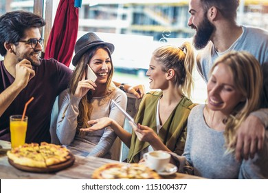Young friends sharing pizza in a indoor cafe