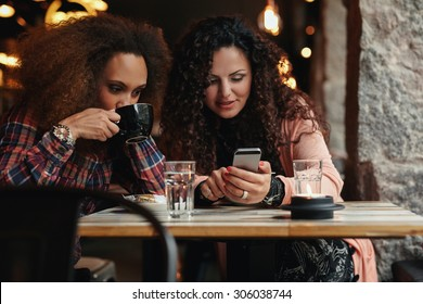 Young friends sitting in a cafe looking at a smartphone. One woman drinking coffee and another holding mobile phone,
