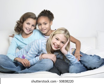 Young Friends sitting, leaning on one another, smiling