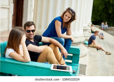 Young friends sitting on bench outdoors, relaxing, talking.