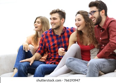 young friends sitting on the couch and rooting for their favorite team