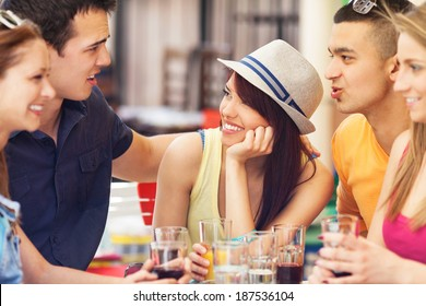 Young friends sitting on table in cafe