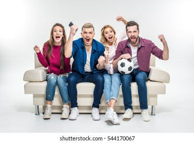 Young friends sitting on white couch with soccer ball and supporting favorite team isolated on grey
