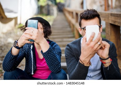 Young friends sitting outdoors on staircase in town, using smartphone.