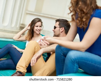 Young friends sitting and talking outdoors on a bench.
