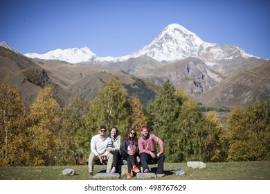 Young friends sitting together with beautiful mountain background with Mt. Kazbek and Gergeti Trinity Church in Stepantsminda, Georgia