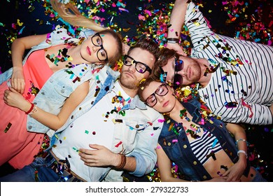Young friends sleeping in confetti on the floor in nightclub after party