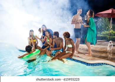 Young friends smiling, rejoicing, resting at party near swimming pool.
