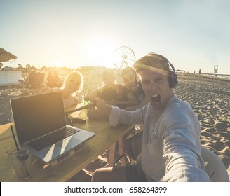 Young friends taking selfie during video live streaming at chiringuito beach party - Man vlogger using phone camera for snapshot at sunset - New social trends concept - Soft focus on left girls