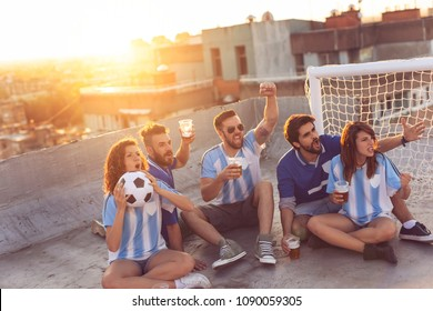 Young friends watching a football match, cheerfing for their team and drinking beer on a building rooftop, with cityscape in the background
