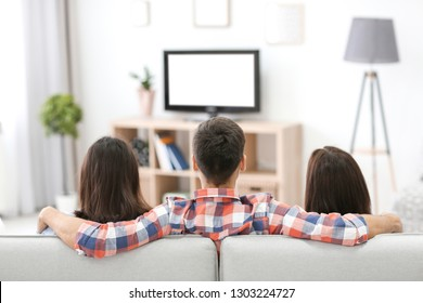 Young friends watching TV at home