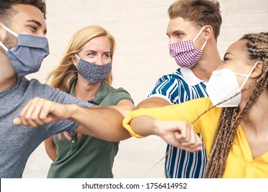 Young friends wearing face mask doing new social distancing greet with elbows bumps for preventing corona virus spread - Physical distance and friendship safety greetings concept
