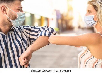 Young friends wearing face surgical mask doing new social distancing greet with elbows bumps for preventing corona virus spread - Physical distance and friendship safety greetings concept