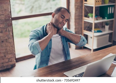 Young frustrated afro american freelancer is having a strong pain in neck. He is at home office, sitting at his modern work station, suffering, massaging it