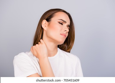 Young frustrated brown haired lady is having a strong pain in neck. She is in a white tshirt, massaging the neck, with pain grimace