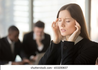 Young frustrated businesswoman feels unwell dizzy during meeting, touching massaging temples, trying to cope with migraine, chronic headache caused by physical emotional work stress, nervous disorder