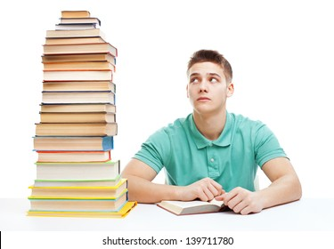 Young frustrated student sitting at the desk with high books stack isolated on white background