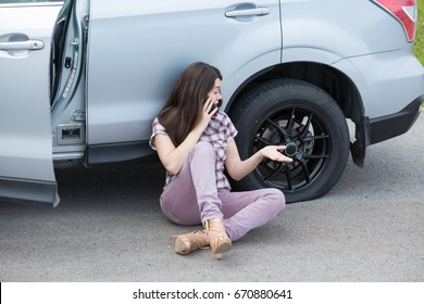 Young frustrated woman with flat tire on broken car phoning for assistance