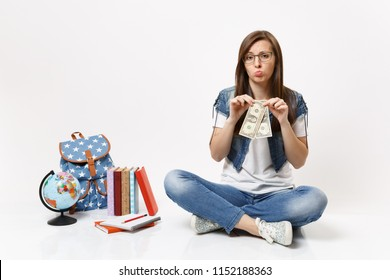 Young frustrated woman student in glasses holding dollar bills have problem with money sit near globe, backpack, school books isolated on white background. Education in high school university college