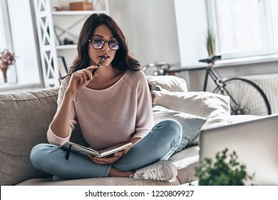 Young and full of ideas. Thoughtful young woman in eyewear studying while sitting on the sofa at home