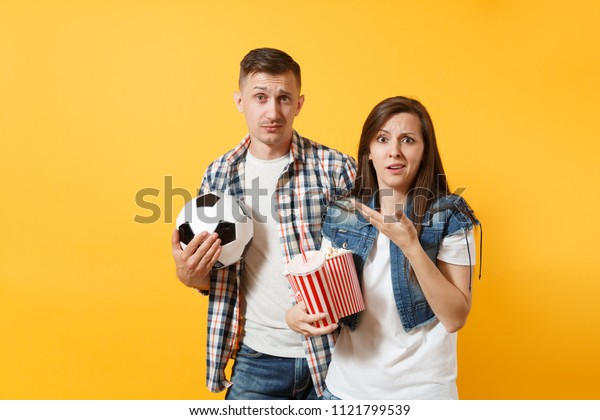 Young fun cheerful couple, woman man, football fans holding soccer ball, bucket of popcorn, cheer up support favorite team, isolated on yellow background. Sport play family leisure lifestyle concept