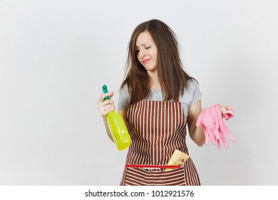 Young fun crazy dizzy loony wild housewife tousled hair striped apron squeegee cleaning rag in pocket isolated on white background. Mad woman spray bottle with cleaner liquid pink gloves. Copy space