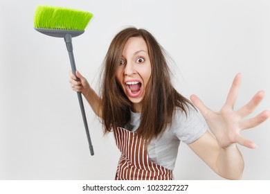 Young fun crazy dizzy loony wild aggressive housewife tousled hair in striped apron pink gloves in pocket isolated on white background. Mad witch woman attack with broom. Copy space for advertisement