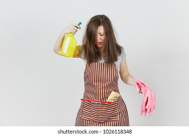 Young fun crazy loony wild screaming housewife tousled hair in apron squeegee rag in pocket isolated on white background. Mad woman shoot from spray bottle with cleaner liquid pink gloves. Copy space