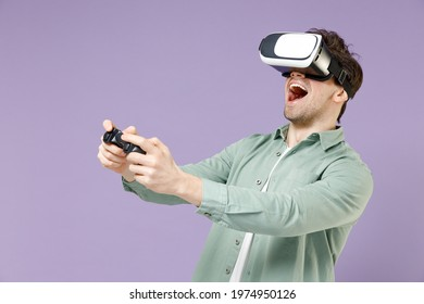 Young fun excited amazed man 20s wear casual green mint shirt white t-shirt playing pc game with joystick console watching in vr headset pc gadget isolated on purple color background studio portrait