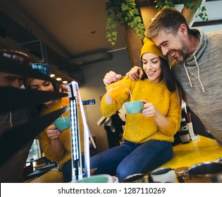 Young fun female barista preparing and pouring milk into hot cup for friend.