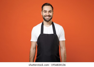 Young fun man 20s barista bartender barman employee in black apron white t-shirt work in coffee shop looking camera isolated on orange color background studio portrait. Small business startup concept