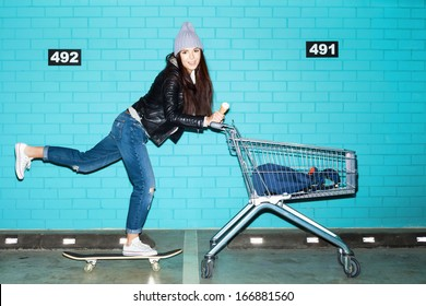 Young funky hipster woman riding skateboard in front pushing shopping cart over blue brick wall. Naughty girl having fun . Indoors, lifestyle