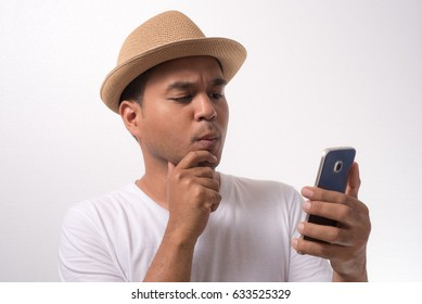 Young funny asian man using smartphone and confused