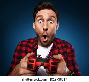 Young funny bearded gamer is playing a video game with his red joystick and he is the happy winner. He is excited to play with his game console, Man with game pad is yelling with joy