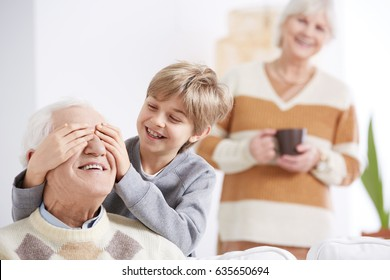 Young funny boy playing with his grandfather in a game