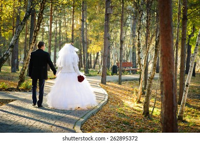 young funny bride and groom having fun in the park