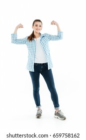 Young funny brunette girl wearing checkered shirt and jeans showing muscles isolated over white
