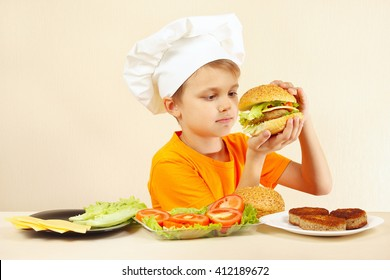Young funny chef expressive enjoys a cooked hamburger
