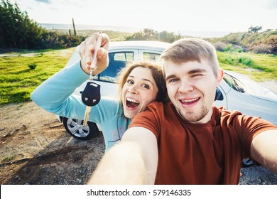 Young funny couple with keys to new car outdoor