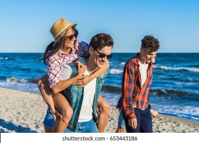 young funny couple in sunglasses piggybacking on the beach. Friends together. Sea is on background. Girl is wearing hat.