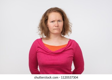 Young funny european woman is offended. She is looking with disbelief at camera. Have some suspicious thoughts