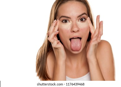 young funny girl applying concealer with fingers under her eyes on white backgeound