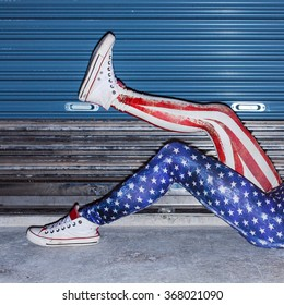 Young funny girl legs in usa style pants and snickers youth lifestyle night urban photo on street background