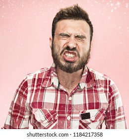 Young funny handsome man with beard and mustache sneezing with spray and small drops, studio portrait on pink background. Comic, caricature, humor. illness, infection, ache. Health concept